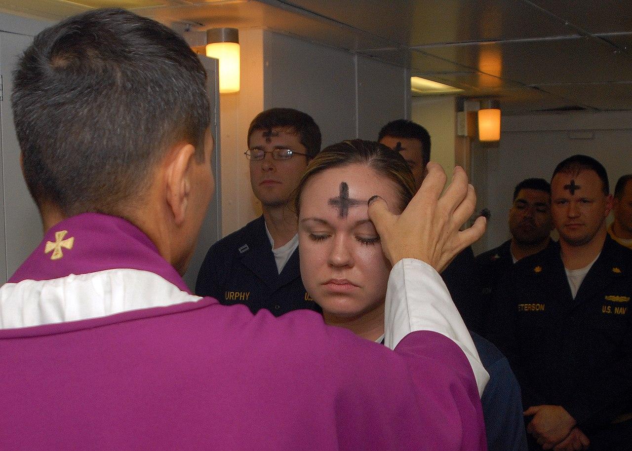 Een priester deelt het askruisje uit